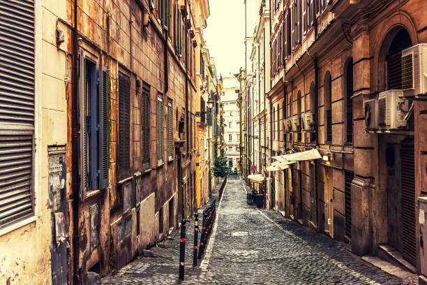 traditional narrow italian street with a cafe and no people - rome road central view foto e immagini stock