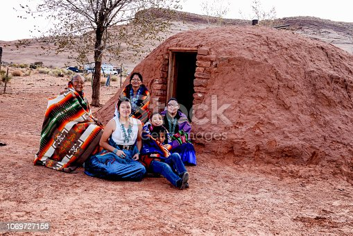 A happy multi-generational family of Native American Navajo people sitting happily outside their traditional Hogan