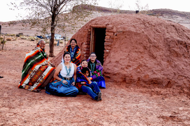 traditional native american family posing outside an authentic navajo hogan - navajo culture stock photos and pictures