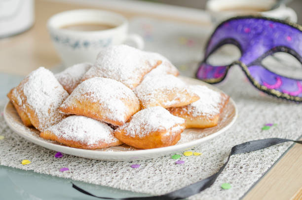 Traditional New Orleans beignets served for Mardi Gras Homemade New Orleans style beignets are small squares of fried dough covered in powdered sugar prepared for Mardi gras. Served on a plate with a cup of coffee,mask and confetti fritter stock pictures, royalty-free photos & images
