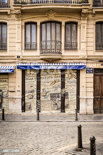 Valencia, Spain - October 25, 2011: The facade to a closed newsagent shop with its shutters drawn in the old district of Valencia, Spain.
