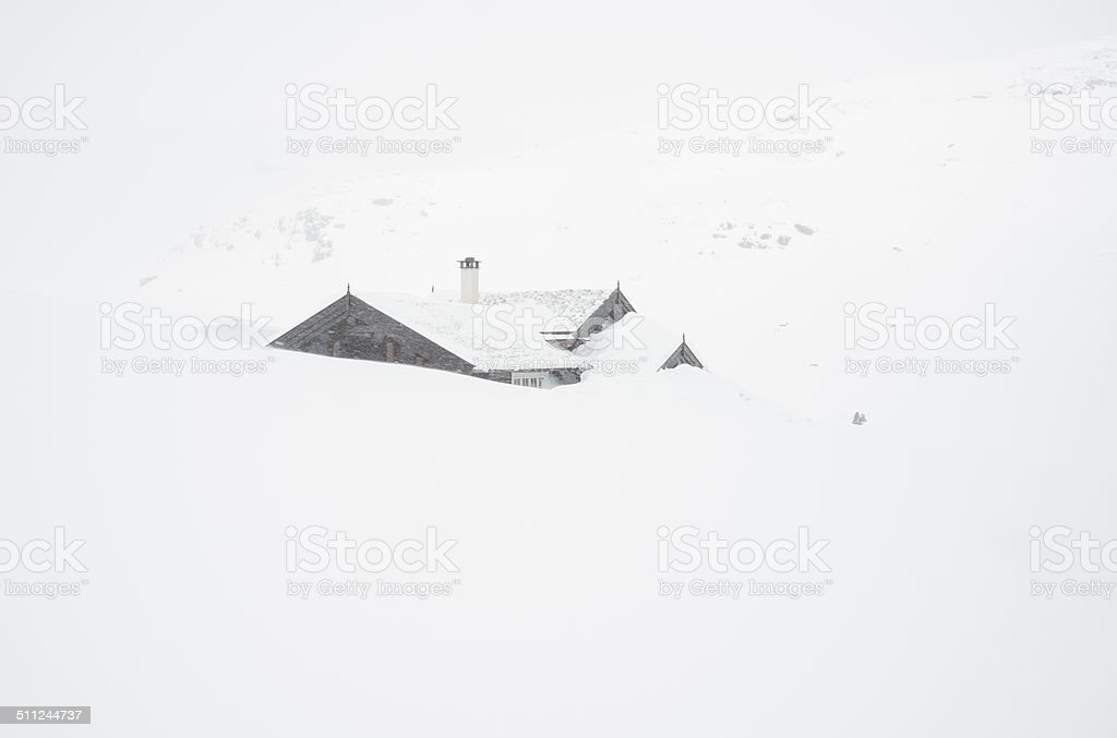Traditional Norwegian wooden log cabin in snow storm stock photo