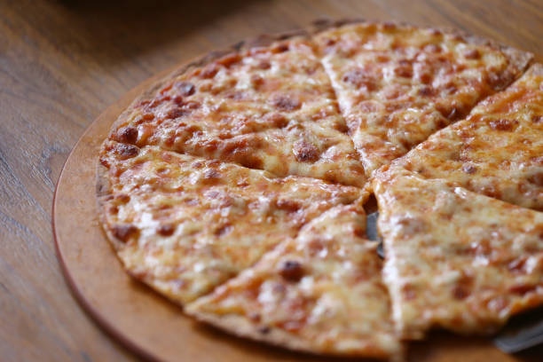 traditional of hot cheese pizza on wooden dish in the restaurant. - frucht pizza cookies stock-fotos und bilder
