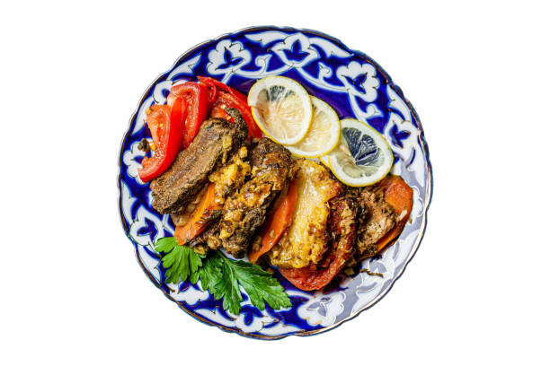 Traditional oriental cuisine. Dish for the holiday of Navruz from meat, fish, pineapple, paprika, tomato and lemon. Serving dishes in Uzbek plates. Copy space, background image Traditional oriental cuisine. Dish for the holiday of Navruz from meat, fish, pineapple, paprika, tomato and lemon. Serving dishes in Uzbek plates. Copy space, isolated image muziekfestival stock pictures, royalty-free photos & images