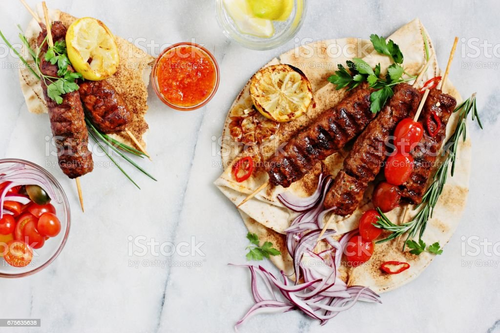 Traditional oriental meat kebab of minced beef or lamb with vegetables and herbs overhead marble cutting boar. - foto de stock