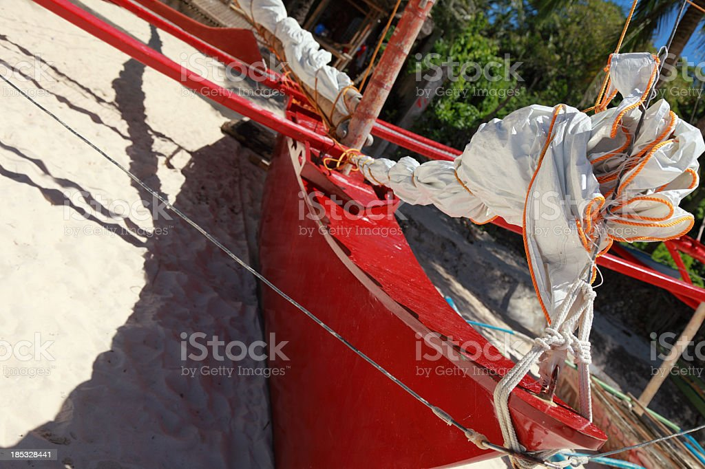 Traditional outrigger sailboat beached on the beach royalty-free stock photo