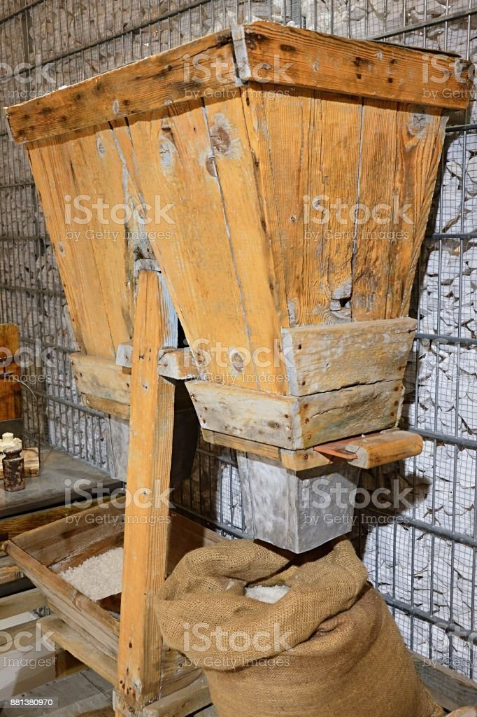 Traditional packaging wooden mechanism used for filling of sacks in natural sea salt production stock photo