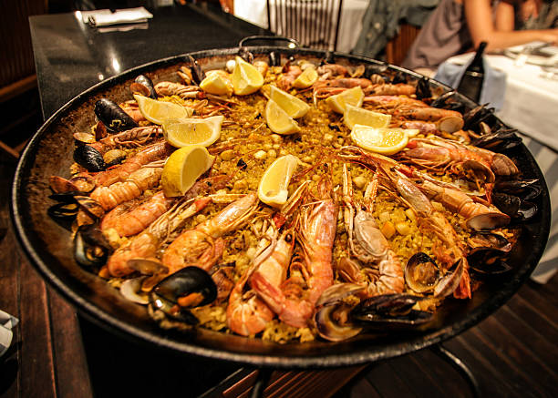 traditional paella served at restaurant in barcelona, spain - paella stock photos and pictures