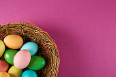 Beautiful easter table composition. Pile of painted eggs of different passtel colors in wicker basket on crimson paper background. Greeting card template. Copy space, close up.