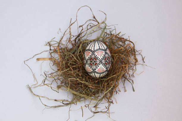 Traditional painted handmade Easter egg on hay stock photo