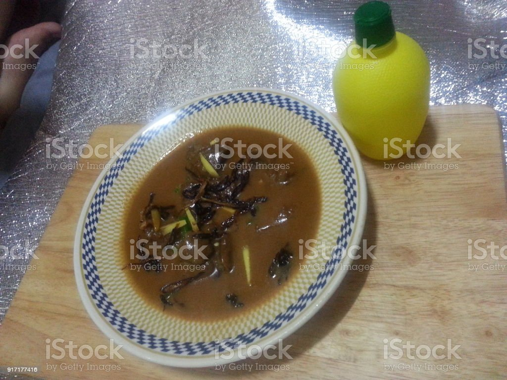 Traditional Pakistani Haleem served with green salad and Lemon juice on a wooden table stock photo
