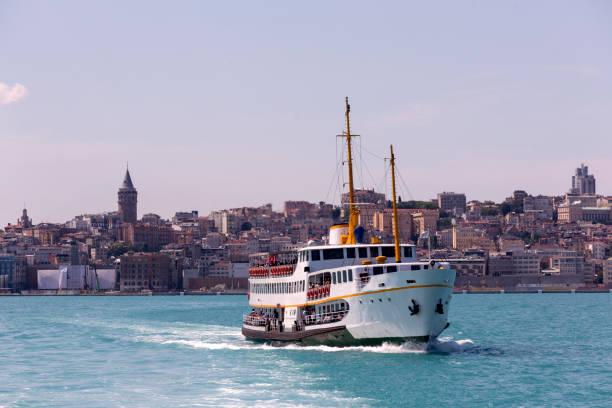 traditional passenger boat at coast of bosphorus near galata tower in karakoy istanbul turkey - каракёй стамбул стоковые фото и изображения