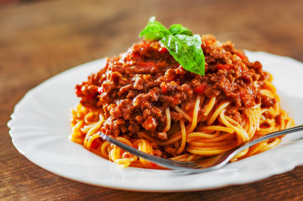 Traditional pasta spaghetti bolognese in white plate on wooden table background Traditional pasta spaghetti bolognese in white plate on wooden table background spaghetti stock pictures, royalty-free photos & images