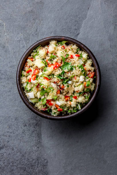 Traditional peruvian quinoa quinua salad in clay bowl, slate gray background stock photo