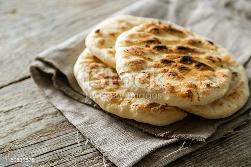 istock Traditional pita bread on rustic wood background 1152832578