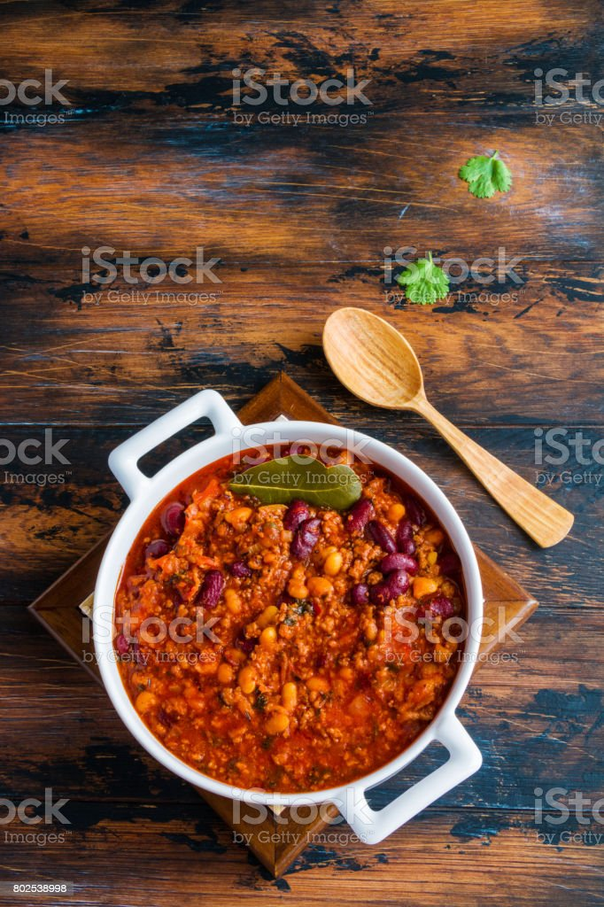 Traditional Polish cuisine, stewed Breton beans  with minced beef, bacon, mashed tomatoes, onion, garlic, paprika, bay leaves and spices. White casserole on wooden rustic table, top view. stock photo