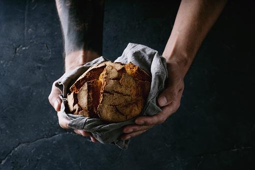 Traditional Portuguese bread Broa de milho in male hands