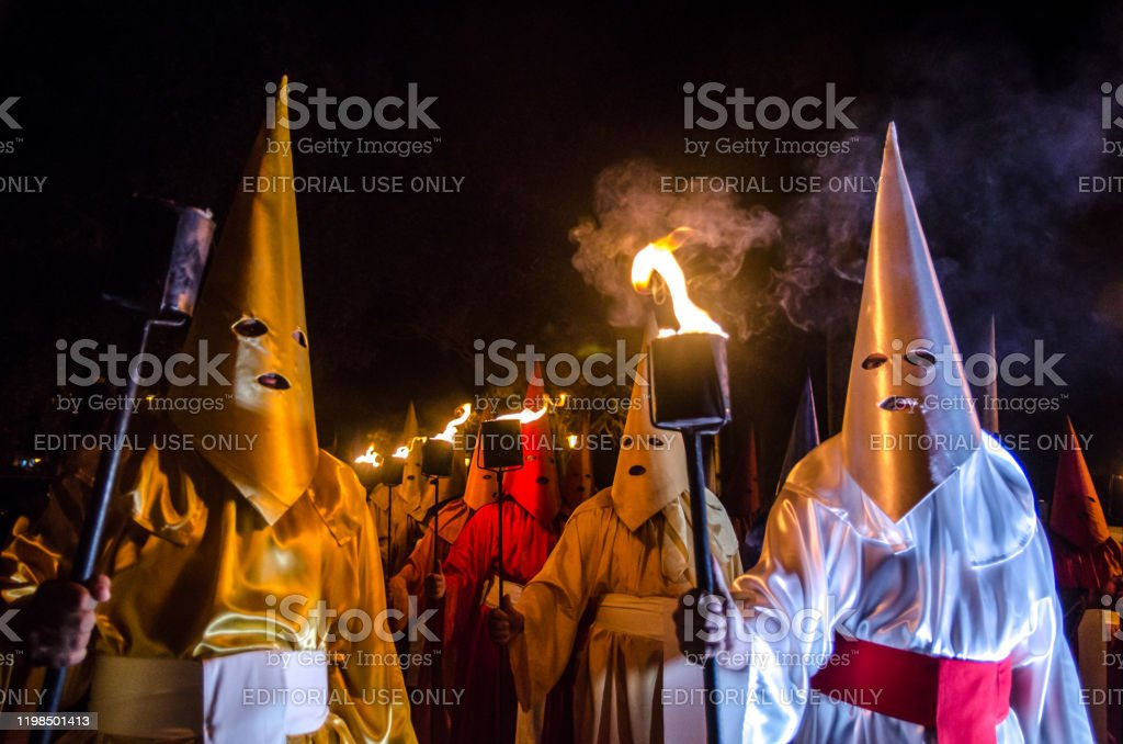 Traditional Procession in the City of Goiás Velho At 0 am on Thursday of Holy Week, the streetlights of the Historic Center of the City of Goiás (or Goiás Velho) go out. At the sound of drums and the light of torches, the Fogaréu Procession begins. Tradition in the city since 1745, the ritual symbolizes the search and arrest of Christ. About 40 hooded men, the farricocos, who represent the Roman soldiers, carry the torches through the city streets, to the sound of drums that dictate the rapid steps of the procession that lasts about 1 hour. Location: Goiás City, Goiás, Brazil. Arts Culture and Entertainment Stock Photo