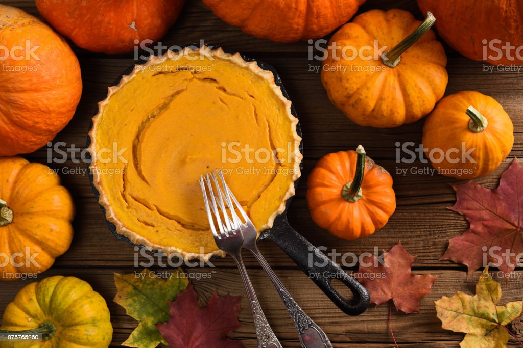Traditional pumpkin pie flat lay. Open homemade pie baked in cast iron pan surrounded with bright pumpkins and marple leaves on rustic background stock photo
