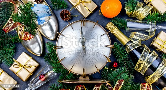 istock NEW YEAR CELEBRATION. Traditional put money to shoe for have money en New Year. Flat lay composition with vintage clock, shoes with dollars, champagne, Christmas decorations 862326544