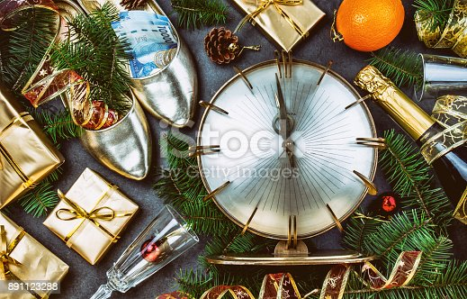 istock NEW YEAR CELEBRATION. Traditional put money to shoe for have money en New Year. Flat lay composition with vintage clock, shoes with chilean money pesos, champagne, Christmas decorations 891123288