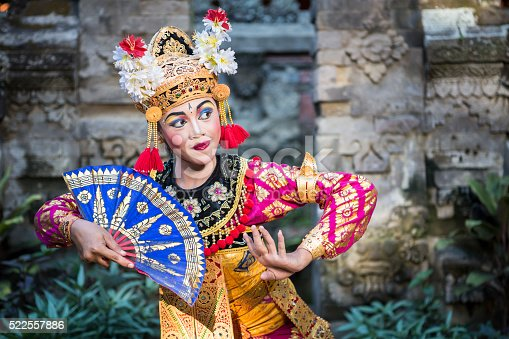 A young Bali female dancer is performing the Ramayana dance in a temple of Bali, in Indonesia. The Hindu culture in Bali is still preserved today and attracts millions of visitors in the Island of Gods for its the culture and natural beauty.