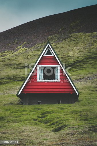 Beautiful view of traditional red A-frame cabin with green meadows and dark moody clouds on a summer day in Iceland