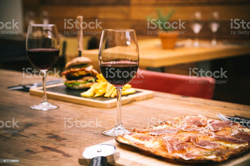 Traditional restaurant atmosphere with ham pizza and burger with chips in the background stock photo