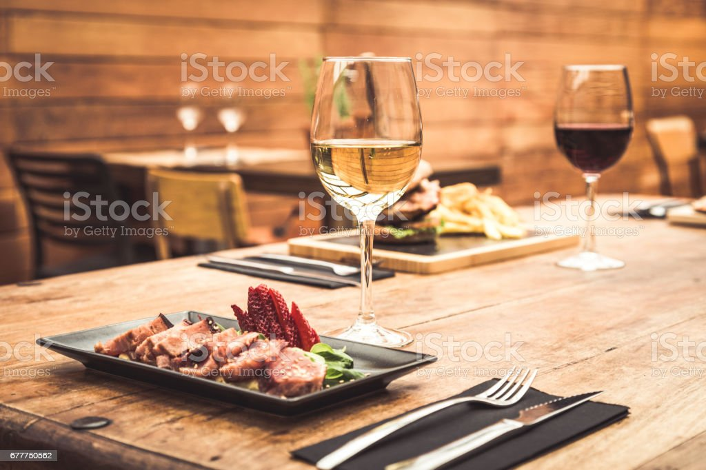 Traditional restaurant atmosphere with tuna tataki and burger with chips in the background stock photo