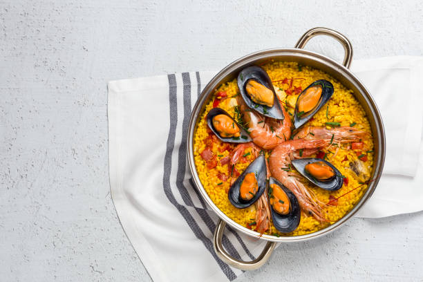 traditional rice in paella with fish and meat. - paella stock photos and pictures