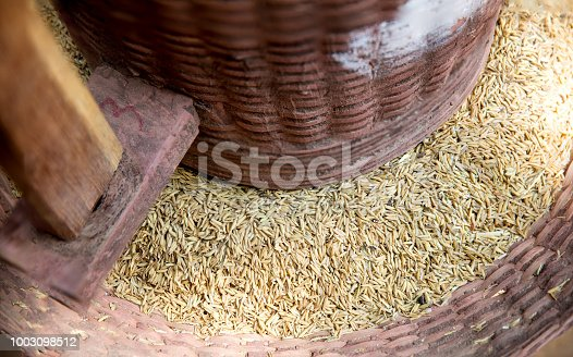 Traditional rice milling with a wooden mortar and pestle.Ancient rice mortar office paddy.Rice Grain on Rice milling machine.