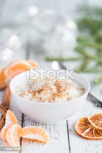 Traditional rice pudding also known as tomtegröt or swedish risgrynsgröt. The rice pudding is in a white porcelain bowl on a white wooden table, with fresh orange slices and dried orange and cinnamon next to the bowl.