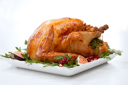 Garnished traditional roasted turkey, garnished with fresh figs, pomegranate, and herbs. On white background.