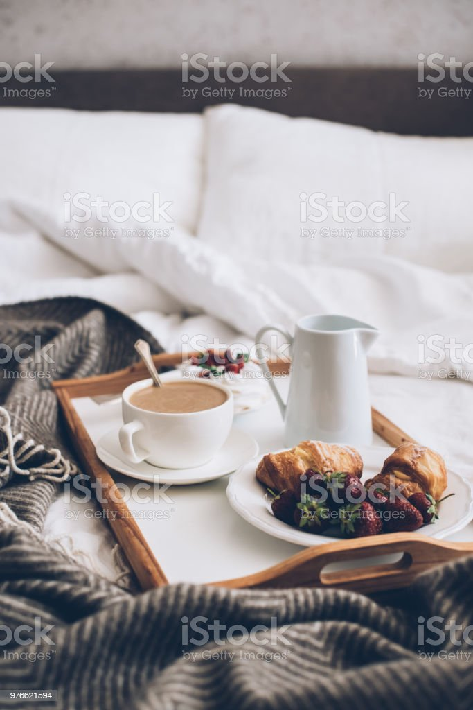 Traditional romantic breakfast in bed in white and beige bedroom stock photo