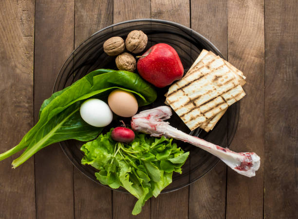 Traditional round seder plate,Passover Traditional round seder plate with six symbolic foods on the brown wooden table. seder plate stock pictures, royalty-free photos & images