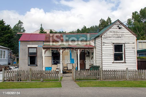 Queenstown, Tasmania: April 03, 2019: A typical detached double fronted bungalow home with a corrugated roof, white picket fence and verandah in Queenstown.