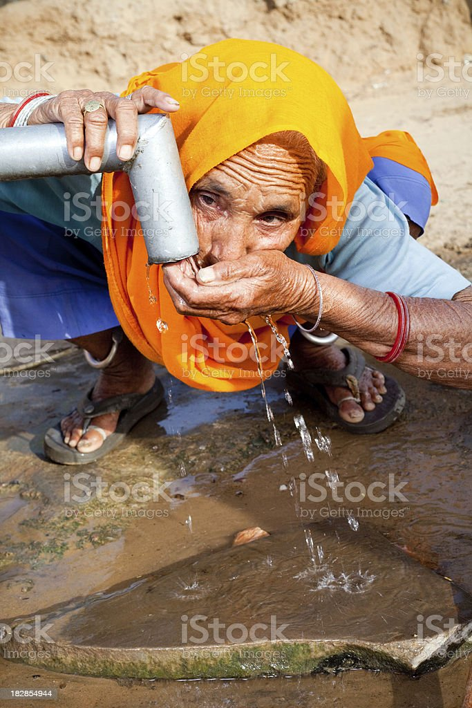Traditional Rural Indian Senior woman drinking water in Rajasthan royalty-free stock photo