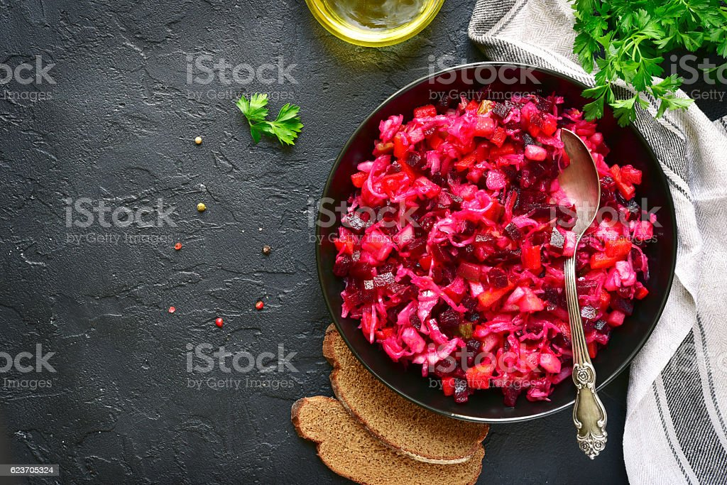 Traditional russian beetroot salad vinaigrette on a dark plate . stock photo