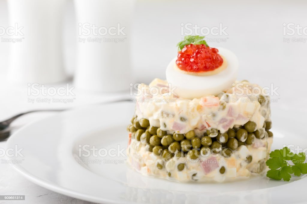 Traditional russian dish Olivier salad served with red caviar on top