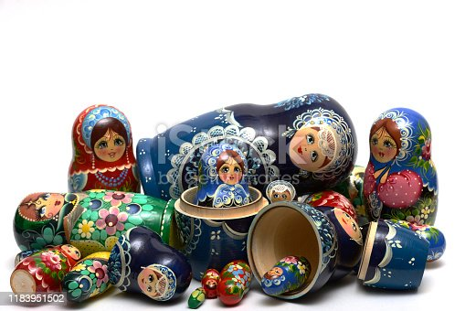 traditional Russian nesting dolls scattered in a mess on a white background