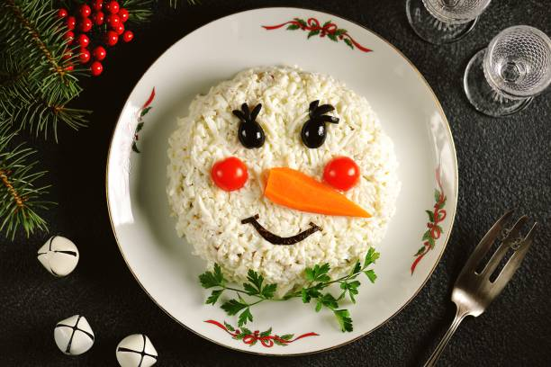 "Traditional Russian New Year's salad ""Snowman"" on an old wooden background. stock photo"
