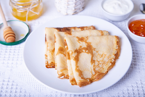 Traditional Russian pancakes with honey, sour cream and jam. shrovetide.