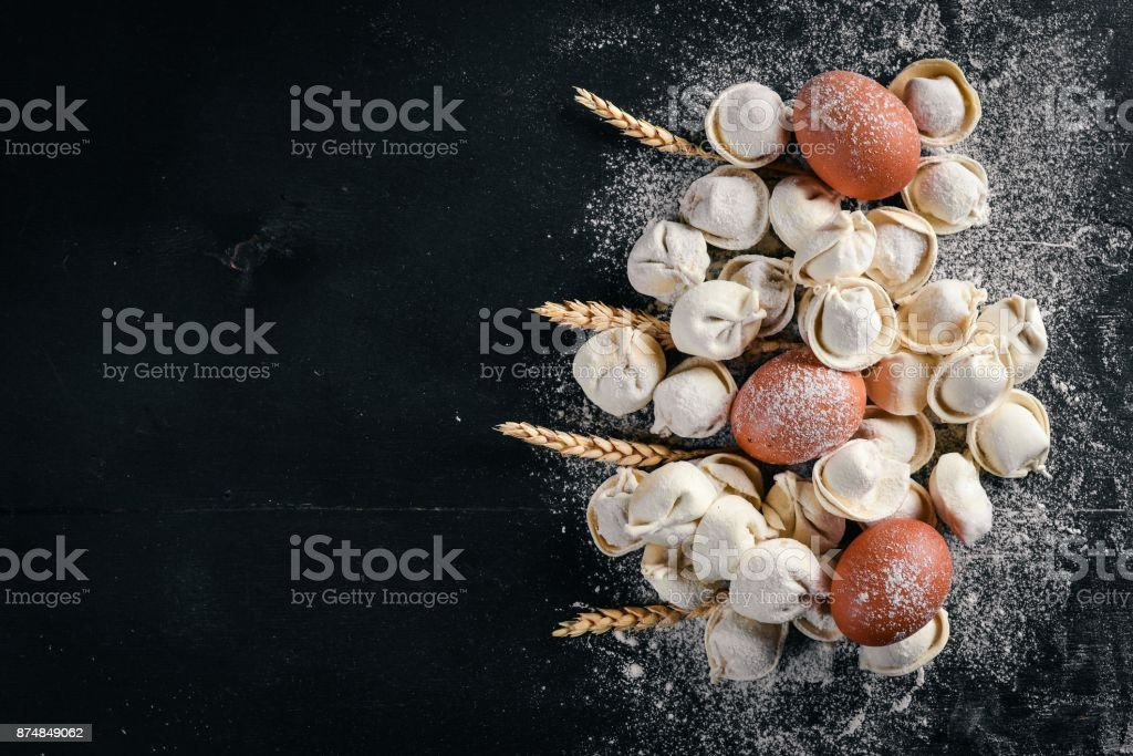 Traditional russian pelmeni, ravioli, dumplings with meat on black concrete background. Top view. Copyspace. stock photo