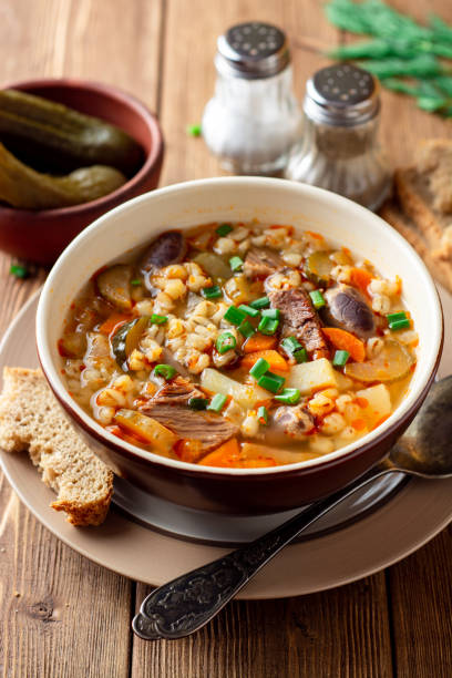 Traditional Russian soup Rassolnik with pickled cucumbers and pearl barley in bowl on wooden table stock photo