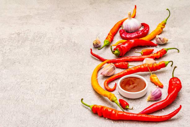 traditionelle sauce sriracha mit zutaten. rote, orange und gelbe chili, knoblauch, meersalz - peperoni stiche stock-fotos und bilder