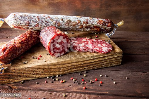 Traditional sausage and sausage with mold. Sliced sausage salami on wooden board with spices. Close-up.