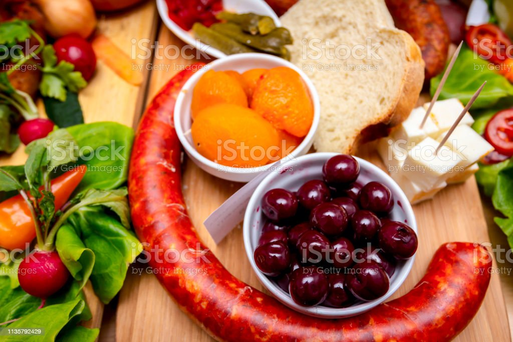 Decorated sausages with fresh vegetables and cherries are exposed on...