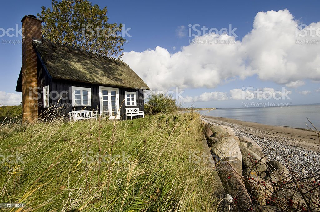 Traditional Scandinavian Beach House Next To The Sea stock photo