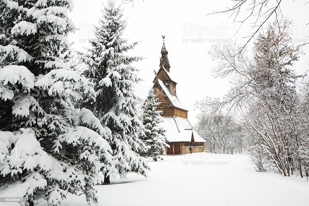 Traditional Scandinavian Stave Church in Winter Snow Forest after Snowfall stock photo