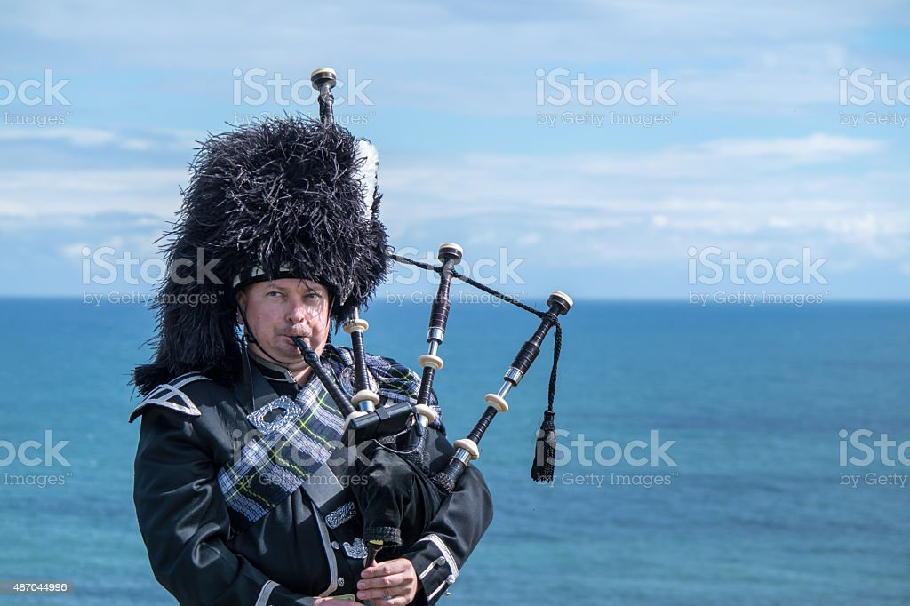 Traditional scottish bagpiper at the sea stock photo